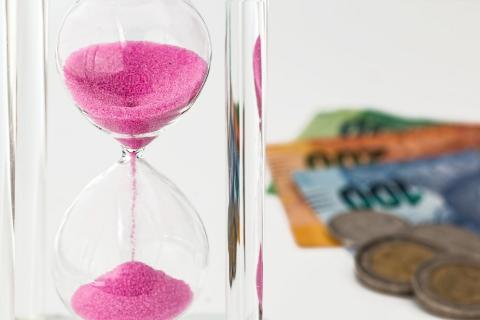 imagen de un reloj de arena y dinero