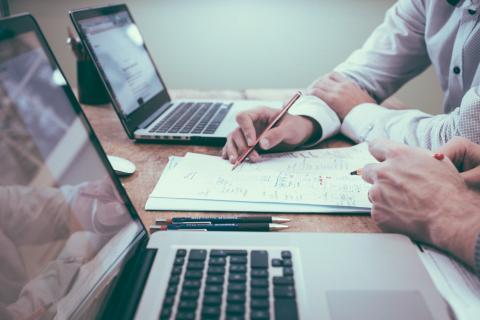 Imagen de dos personas trabajando con un ordenador y documentos
